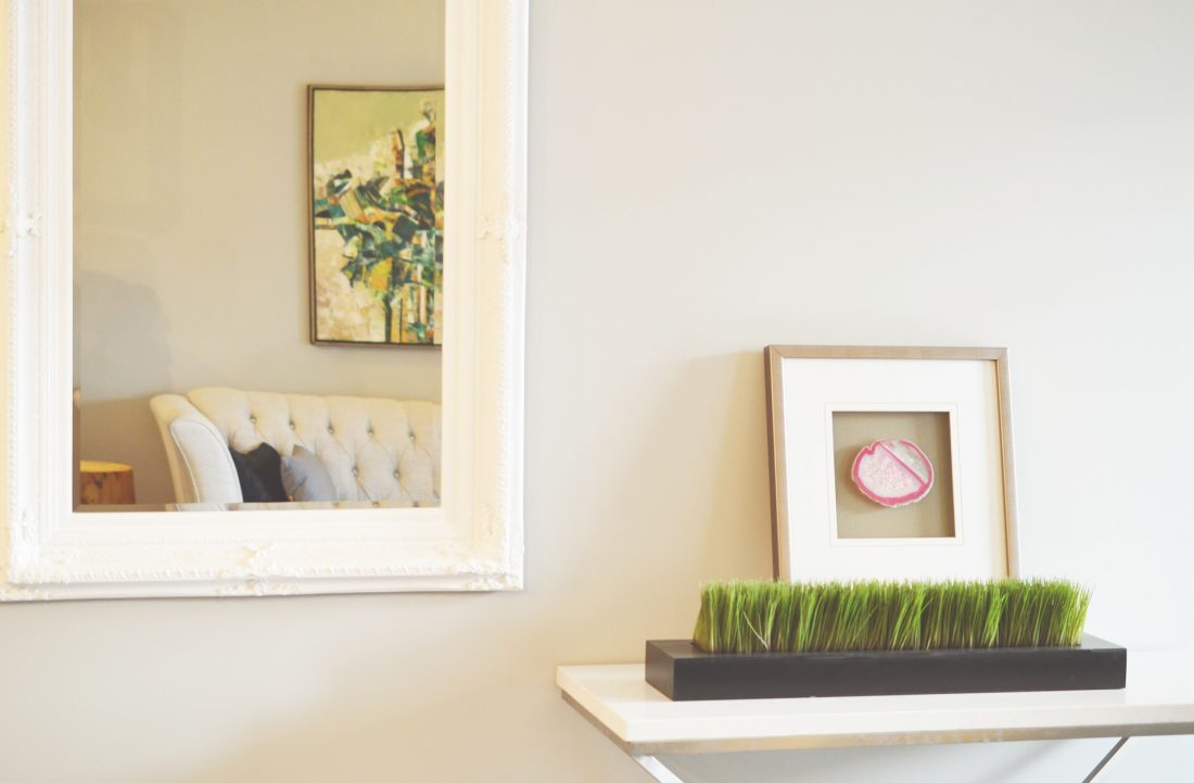 Mirrors on the wall in the living room help to brighten the room.